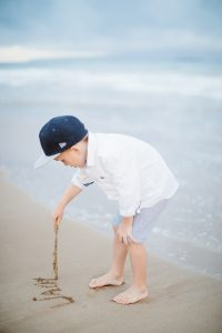 Little boy writing in the sand at the beach