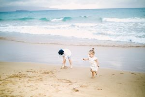 two little kids running on beach by ocean