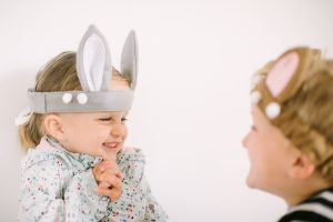 cute little girl in bunny ears looking at brother