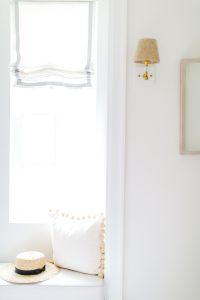 white window seat with pom pom pillow and straw hat