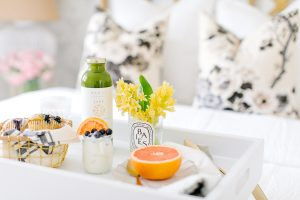 White tray with fresh juice and grapefruit on bed