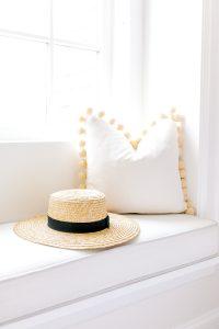 white pom pom pillow on window seat