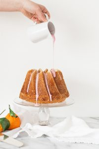 pouring pink citrus glaze on bundt cake