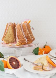 bundt cake on glass cake stand, citrus fruit