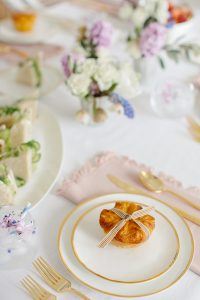 gold rimmed plates and flatware with blush napkin
