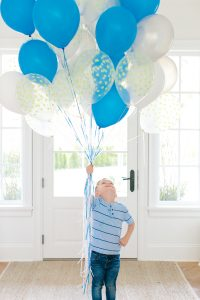 little boy holding blue and white balloons