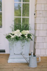 planter with watering can in front