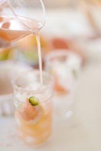 pouring grapefruit juice over ice in margarita