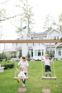 mom pushing kids on swing set