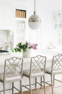 white kitchen with lilacs on counter