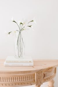 crepe paper daisy on wooden console table