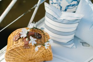 picnic basket on boat with stripped pillows