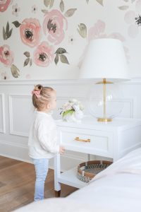 little girl with bow in her hair by bed