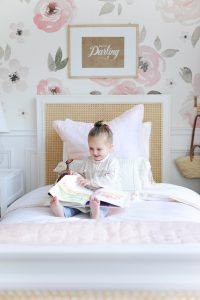 little girl reading book on bed