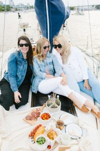women on sailboat with charcuterie platter