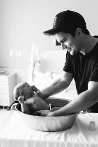 dad bathing newborn