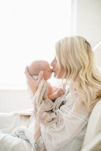 mom kissing newborn forehead