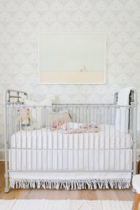 newborn in metal crib in coastal nursery