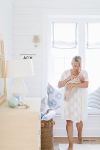 mom waking with newborn in nursery