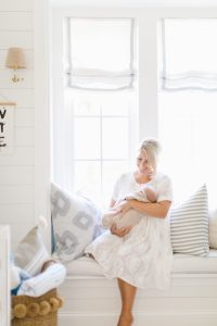 mom sitting on window seat with newborn