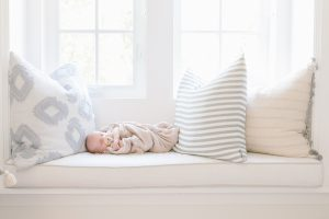 baby on window seat with pillows