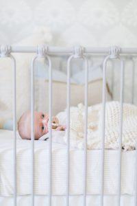 newborn in grey metal crib