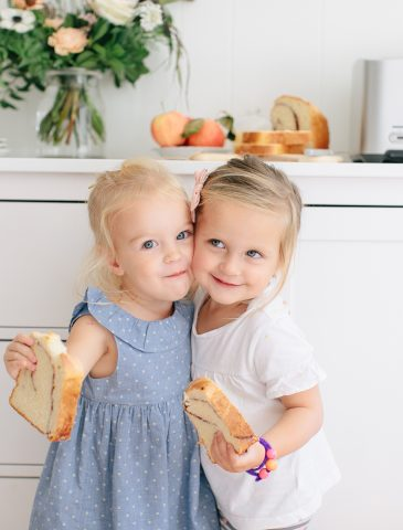 two little girls hugging with toast in their hands