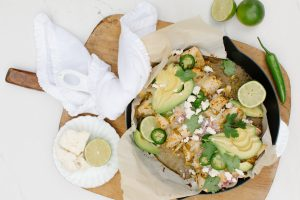 Green chili chicken enchiladas in skillet