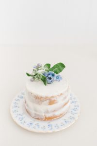 mini vanilla cake with small blue flowers and blueberries
