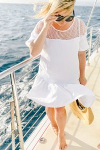 women on boat in white drop waist dress