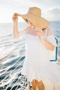 woman wearing overside straw hat with white drop waist dress