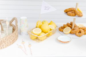 tabletop with 25 cent flag in a basket of lemons and 2 tier plate of donuts