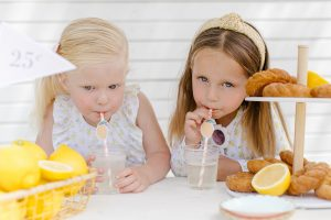 two young girls drinking lemonade