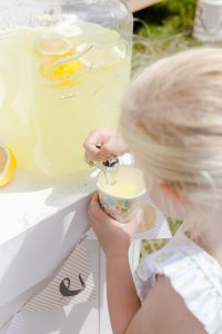 young girl getting a cup of lemonade from a jug