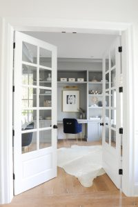 white entrance to a home office space with a grey shelving wall unit and desk and blue chair