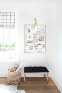 Inspiration board in a corner with a basket and an ottoman seat