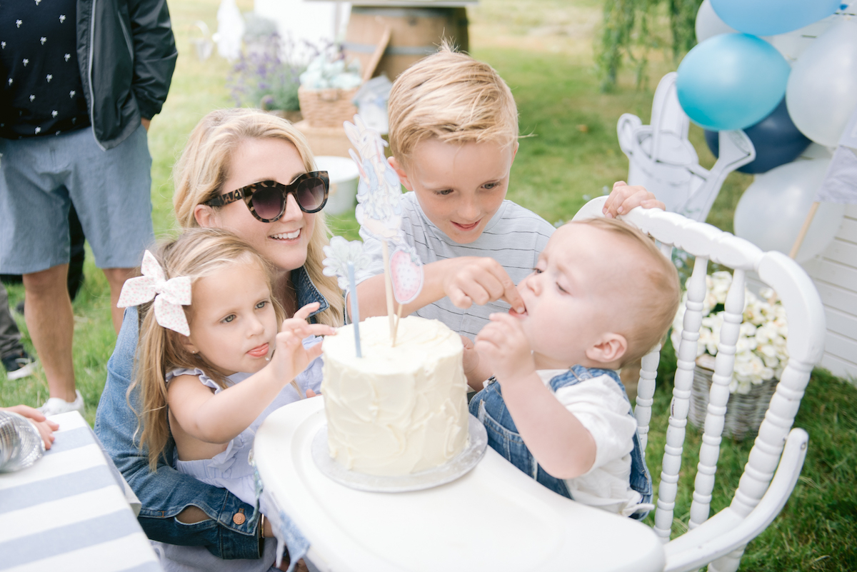 older siblings feeding birthday baby cake