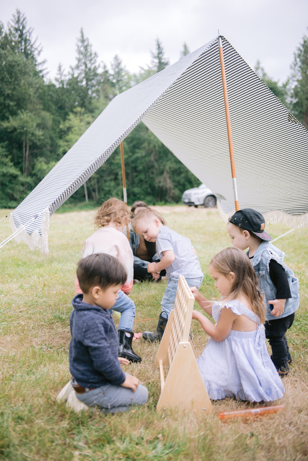 kids playing connect four with a striped tent in the back