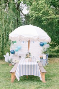 peter rabbit themed picnic tables with blue and white table clothes and umbrellas