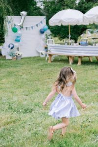 small girl in cute dress running in grass