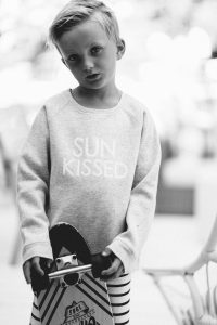 young boy with skateboard longboard and sun kissed crew neck sweater