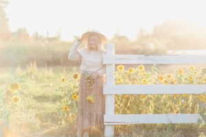 Blonde Woman wearing country girl sweater hat and floral skirt standing in front of sunflowers by a white fence in golden hour