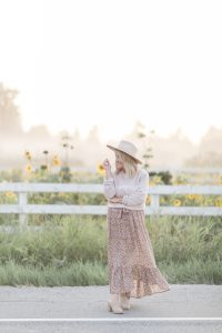 woman wearing a beige hat, country girl sweater and floral print skirt standing in front of a sunflower farm