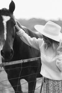 black and white photo woman wearing a hat country girl crew neck sweater and floral print skirt while petting a horse