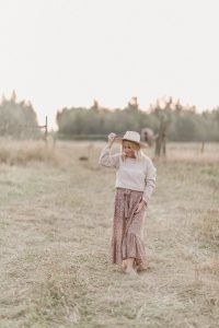 woman wearing a beige hat, country girl sweater and floral print skirt standing in a grassy field