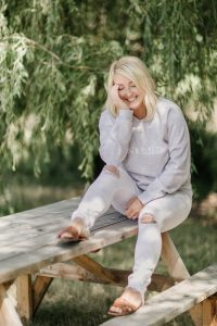 blonde woman smiling sitting on picnic table under a willow tree wearing white ripped jeans with sun kissed sweater