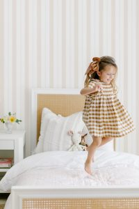 Little Girl Jumping on Bed with #MHxUrbanWalls Brighton Stripes Wallpaper in Vanilla Blush in Background