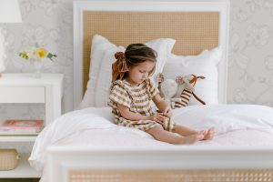Little Girl Playing on Bed with #MHxUrbanWalls Magnolia Wallpaper in Grey